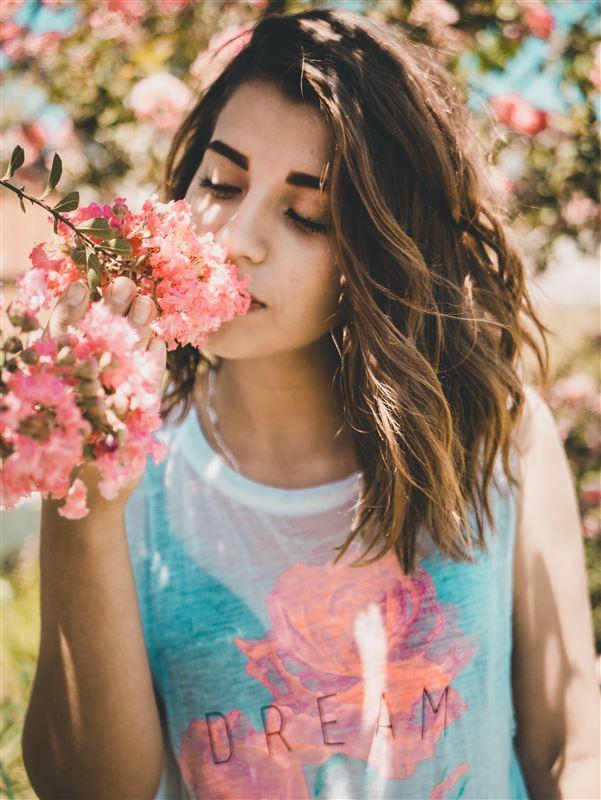 En kvinde dufter til en blomsterranke
