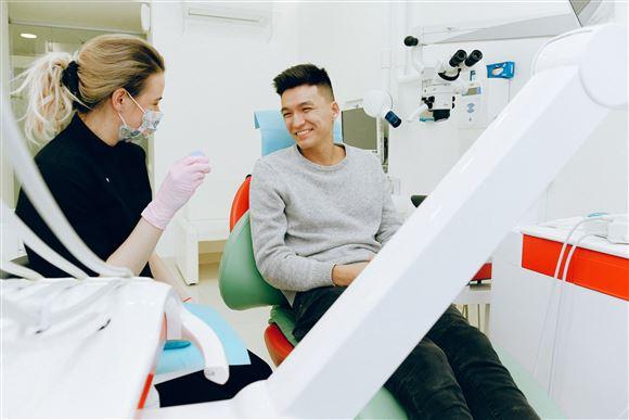 Mad i tandlæge stol med tandlæge ved siden af.