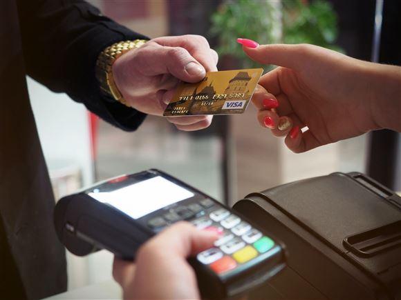 Mand bruger kreditkortterminal.