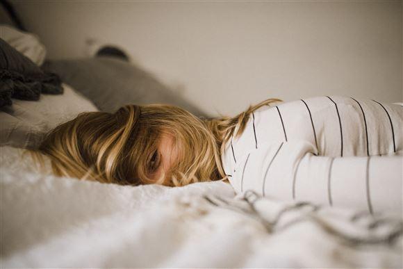 En ung kvinde ligger på en seng på maven med åbne øjne.