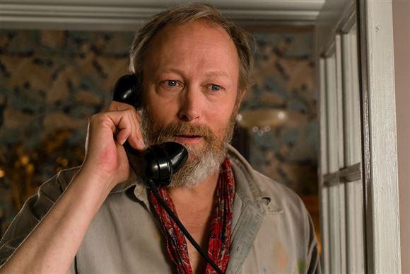 Lars Mikkelsen i kostume fra Badehotellet. Her taler han i telefon.
