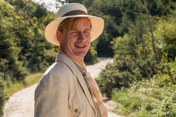Skuespilleren Andreas Jebro i kostume med lys sommerhat og hør habit.