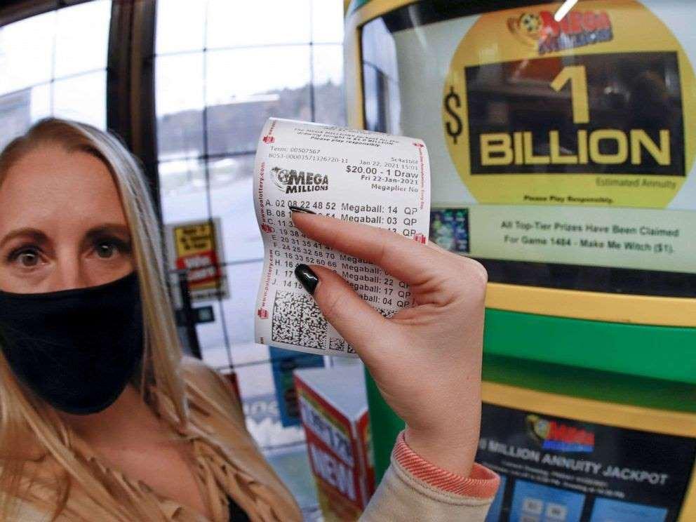 kvinde med mundbind viser lottokupon