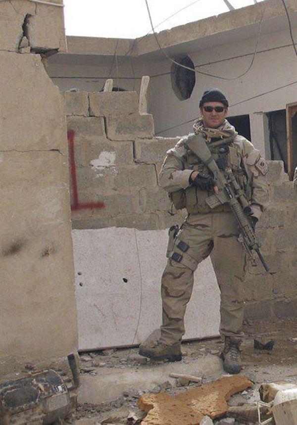 En soldat med en riffel i en sønderskudt bygning