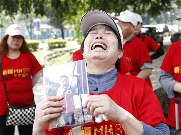 En kvinde græder,. mens hun holder et fotografi af en lille dreng i hånden.