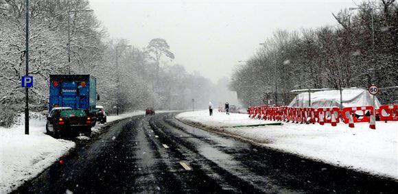 Biler holder i vejsiden med sne overalt