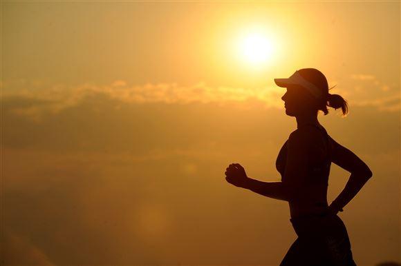 Kvinde løber i solnedgangen