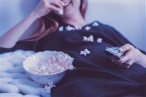 En dame ligger med en fjernbetjening og en skål popkorn på en seng. Der er popcorn overalt.