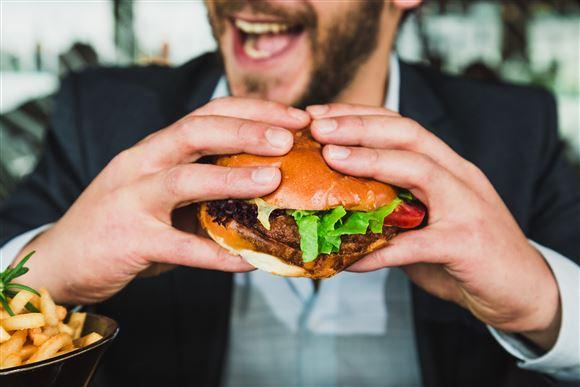 Mand smiler mens han æder en burger