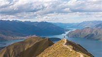 mand står på bjergtop med udsigt over sø