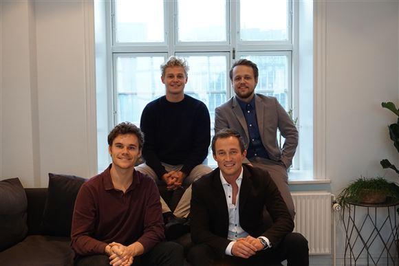 Fire yngre smilende mænd i et kontor