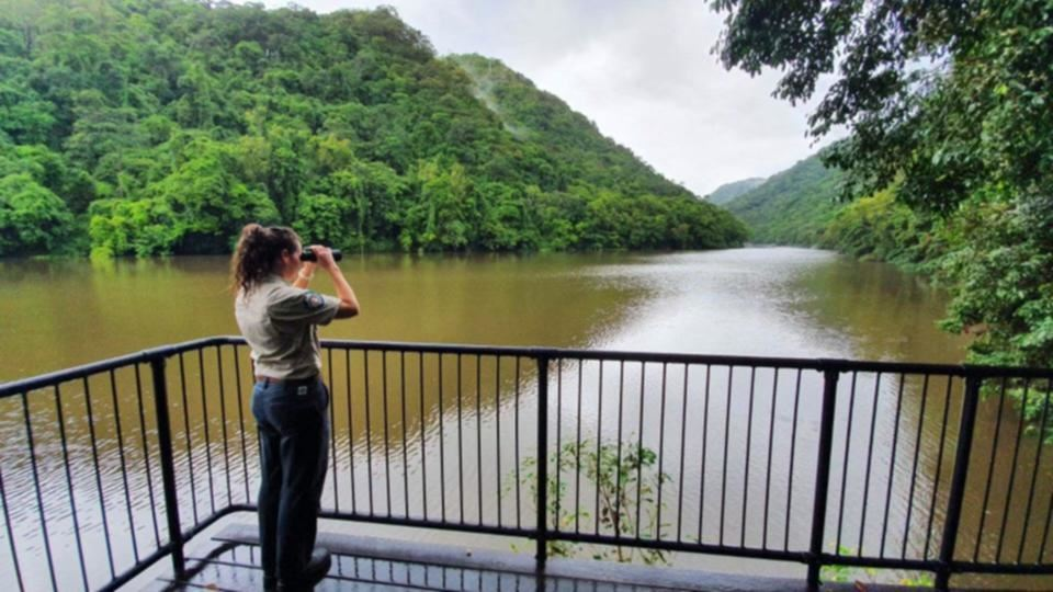 en kvinde med kikkert kigger ud over sø
