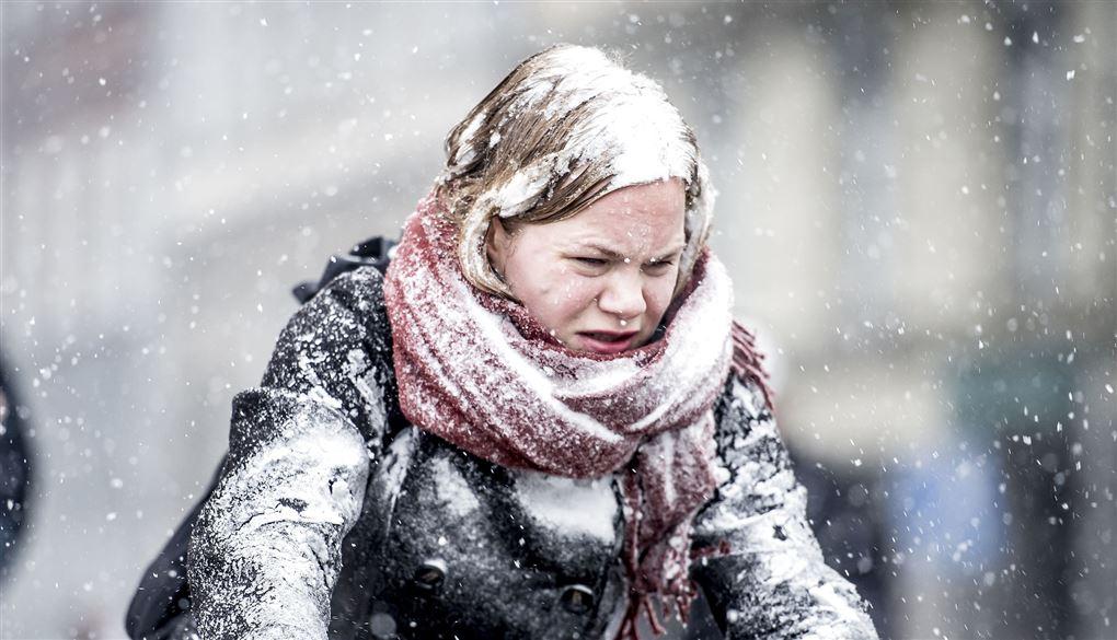 kvinde cykler i snevejr