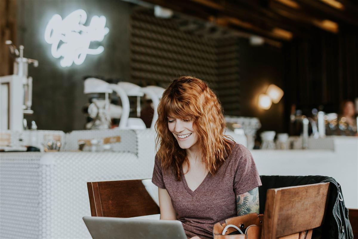Kvinde sidder med computer på cafe
