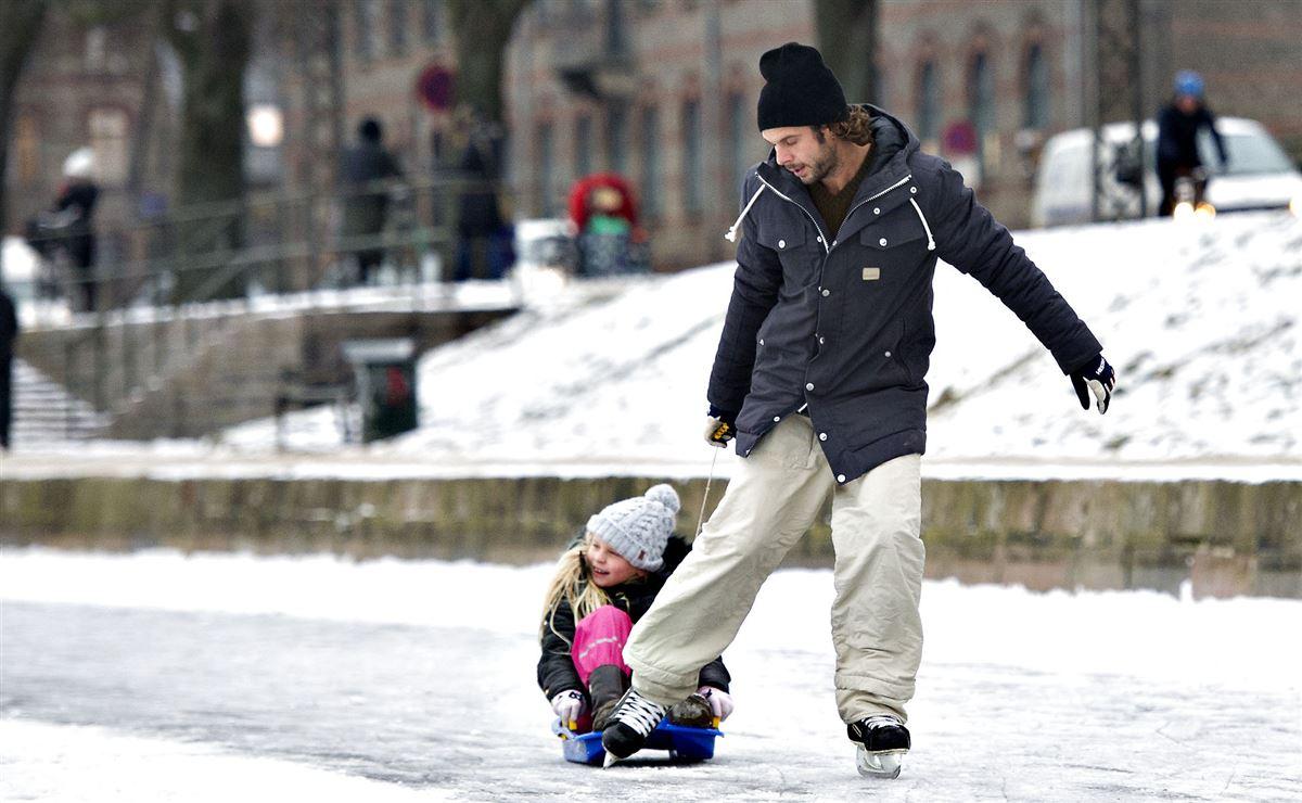 En mand trækker sin datter på isen i en kælk