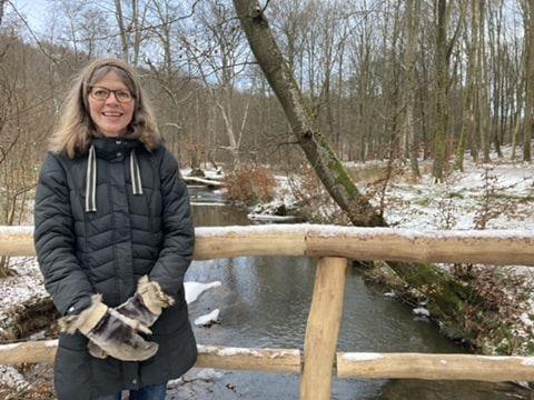 kvinde med briller står på bro