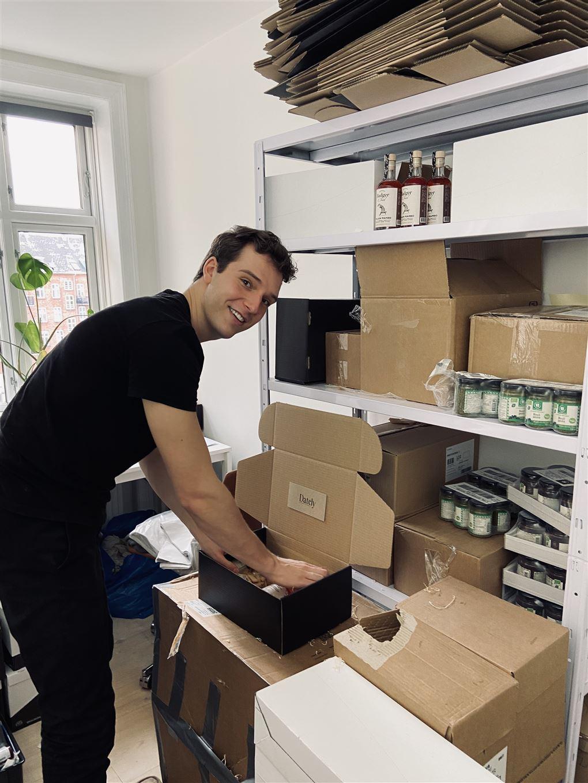 En smilende ung mand pakker papkasser