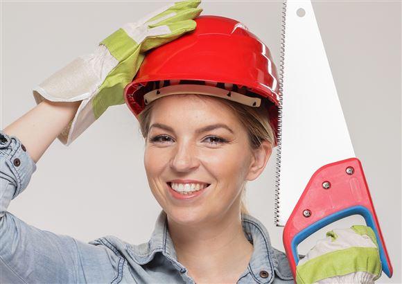 En smilende dame med en arbejdhjelm på hovedet