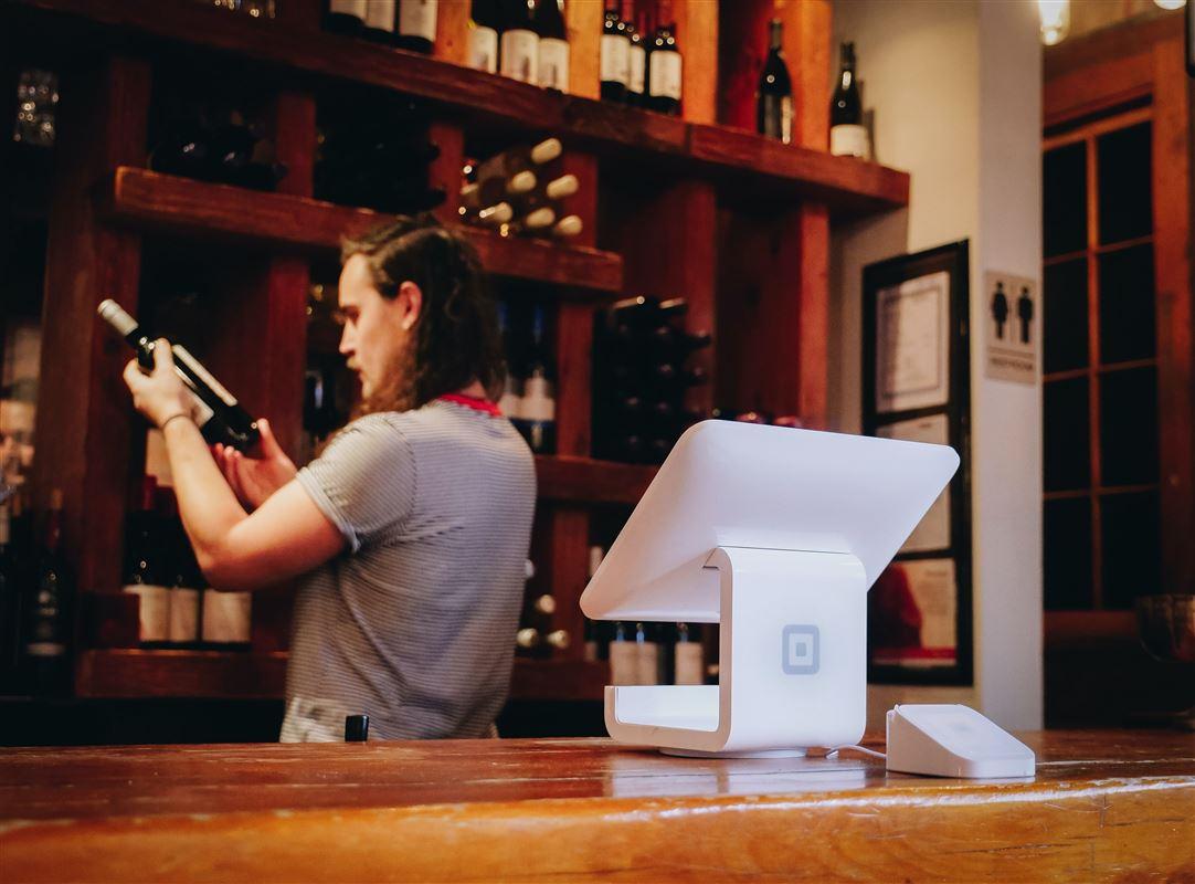 En mand kigger på en vinflaske i en butik