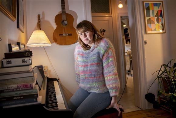 Hjemme hos Katrine Muff Enevoldsen. Hun sidder ved et klaver. Bag hende hænger en guitar på væggen.