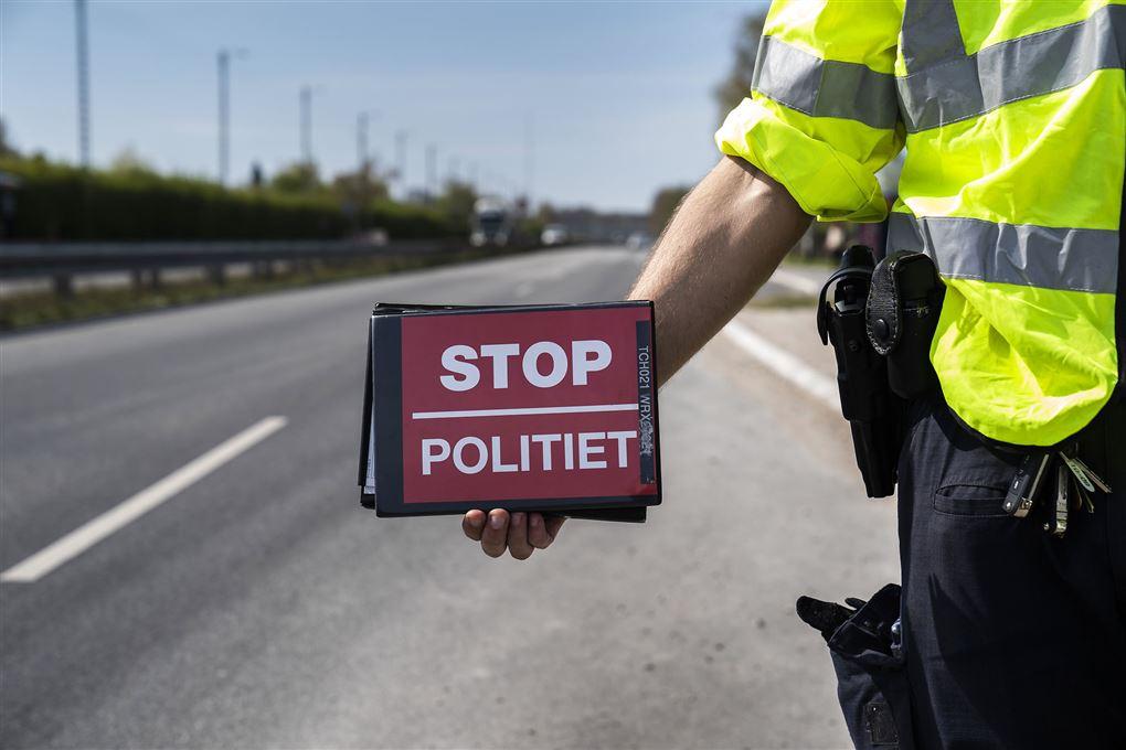 "politimand med skilt med påskriften ""Stop - politiet"""