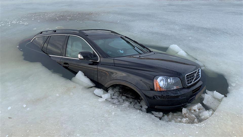 En sort Volvo næsten dækket af vand og omgivet af is.