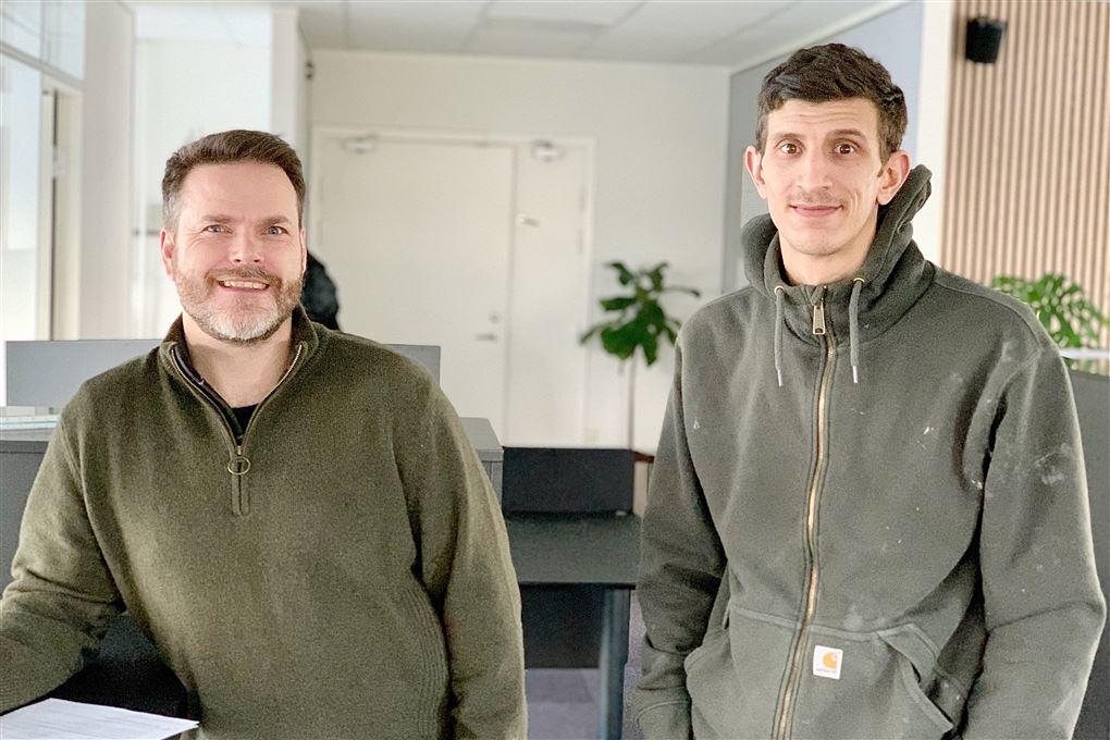 To mænd i grønne fleecetrøjer på et kontor
