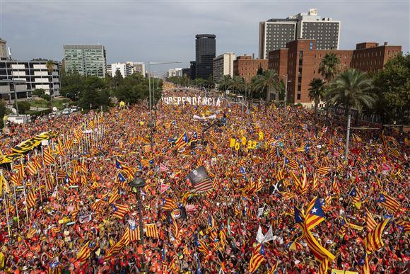 En catalansk menneskemængde med bannere og flag i Barcelonas gader
