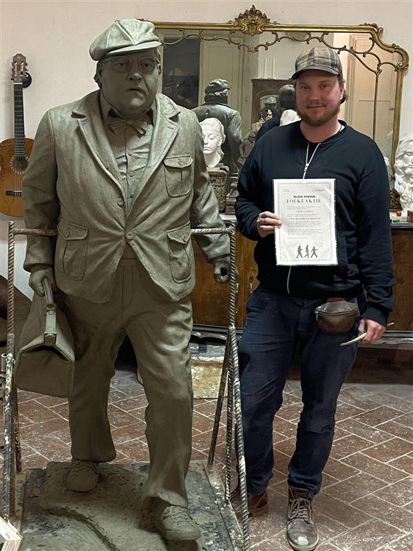 En mand ved siden af en stor bronzeskulptur