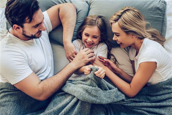 Far og mor ligger i en seng på hver sin side af en lille pige.