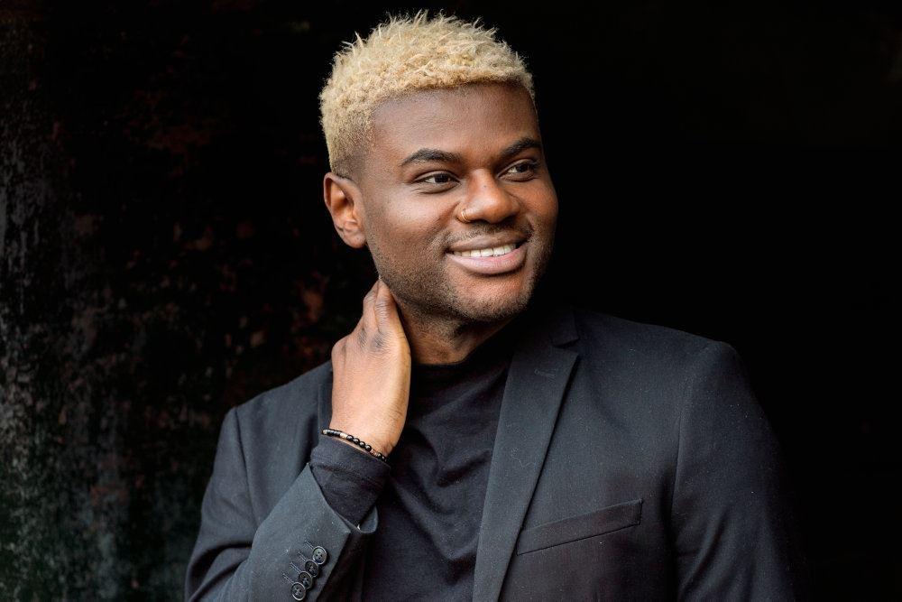 Portræt af Jean Michel han har farvet håret blond og er iført mørkt tøj og står op ad en mørk baggrund.
