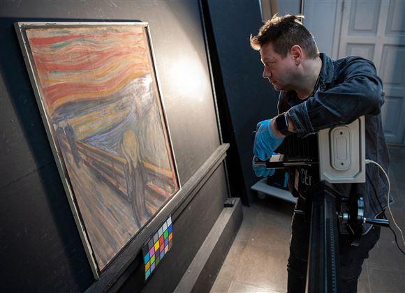 mand undersøger maleri med infrarød scanner