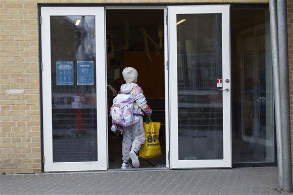 barn med pose på vej gennem dør