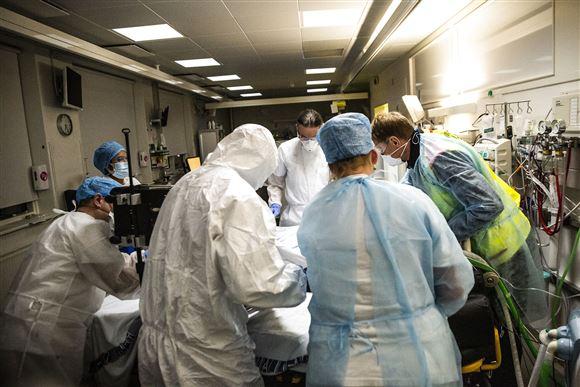 en masse læger og sygeplejersker iført værnemidler står om en hospitalsseng.