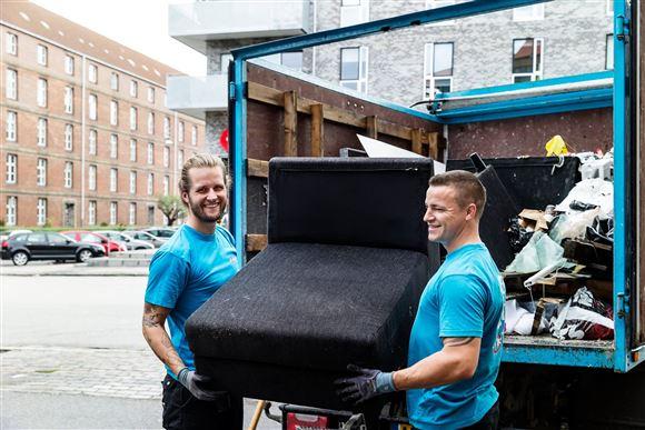 To smilende yngre mennesker slæber en sofa ind i en lastbil