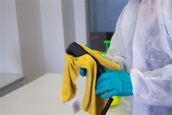 Kvinde med plasthandsker rengør en ting.