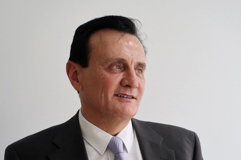 Pascal Soriot med tilbagestøget mørkt hår iført jakkesæt, skjorte og slips.