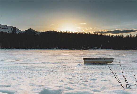 båd ligger på tilfrosset sø