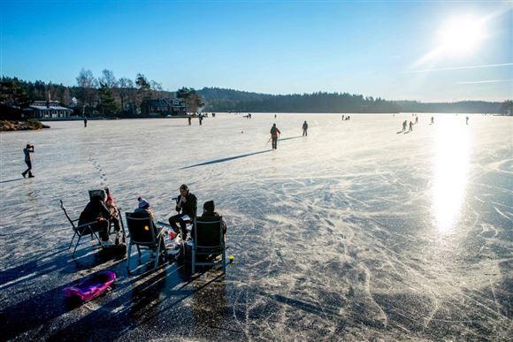 Folk på isen på en svensk sø i solskin