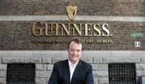 En smilende mand foran Guinness-skilt