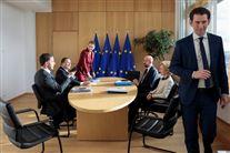Nogle kvinder og mænd i et rum med EU-flag for enden af et bord
