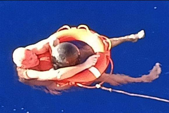 Mand i havet klamrer sig til redningskrans