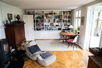 En stue med sofa, to stole, bord, plante og en smart lampe henover bordet