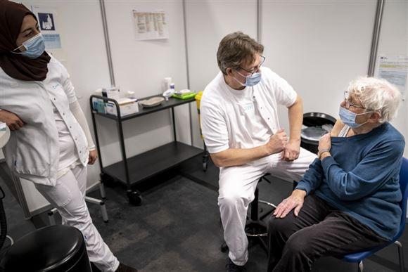 kvinde venter på at få vaccination i lokale med to sundhedspersonaler