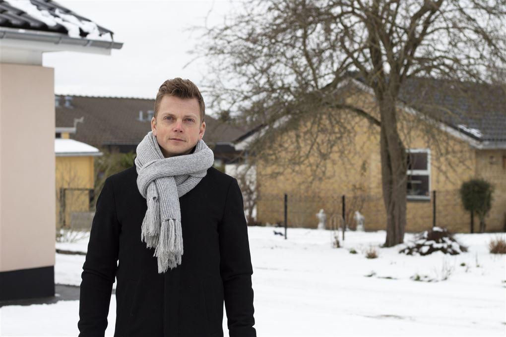 En fyr i frakke, halstørklæde stående i sneen