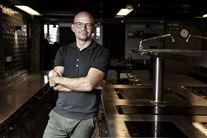 Kokken Jesper Vollmer læner sig op ad et køkkenbord.