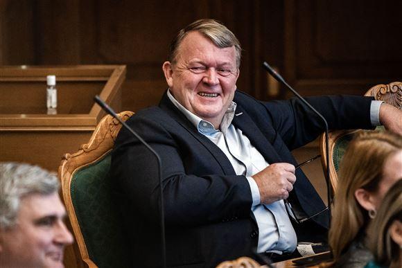 Lars Lække Rasmussen fotograferet i Folketingssalen med et kæmpe, snedigt smil.
