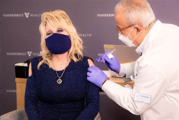 Dolly Parton med sort mundbind får en vaccine