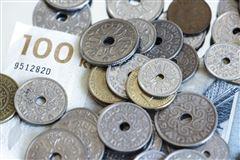 En bunke danske penge. Der er både mønter og sedler.