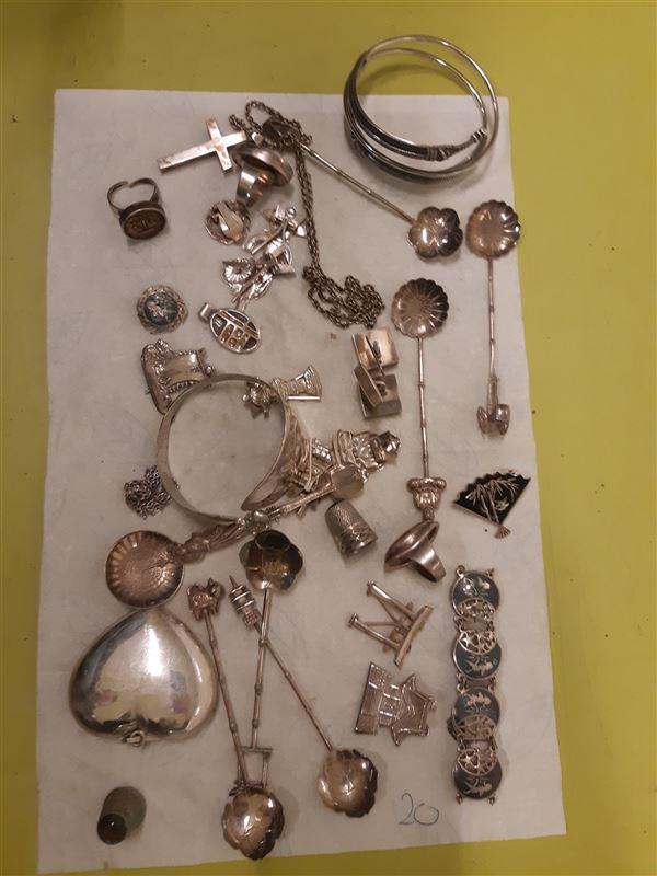 En del af den fundne sølvskat, der består af forskellige smykker og andre effekter. Fotograferet på et hvidt klæde på et bord.